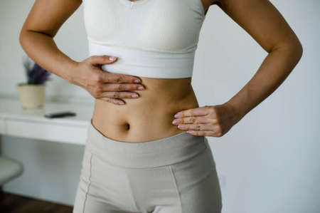 Beautiful Woman In Underwear Testing Fat Layer On Waist.