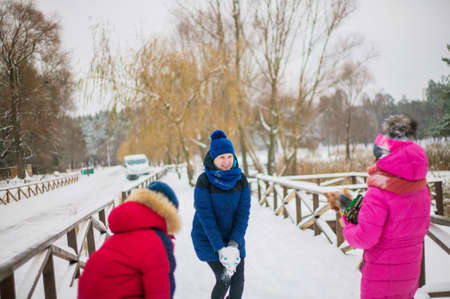 Happy cheerful family with children and dog having fun on snow in park in winter.