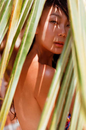 A asian woman is hiding behind palm leaves. Eastern beauty and skin care.