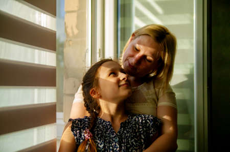 Mother and daughter sitting on sill near window in room. They show emotions and have fun.