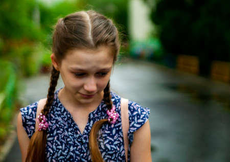 teenager problems - sad teenage girl cries with her worried mother on the background.