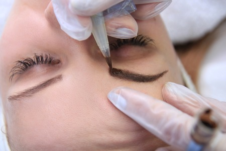 up: Cosmetologist applying permanent make up on eyebrows eyebrow tattoo