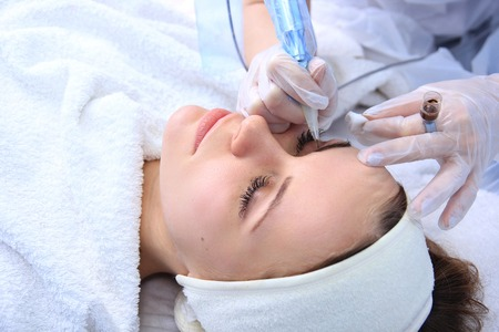 cosmetologist: Cosmetologist applying permanent make up on eyebrows eyebrow tattoo