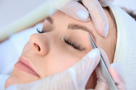 Young woman plucking eyebrows with tweezers close up. Stock Photo