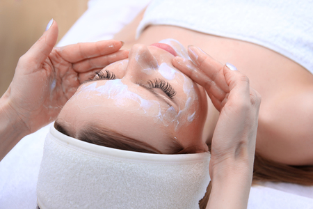 Beautician makes cleansing and exfoliating facial for beautiful girl. Beauty salon. Stock Photo