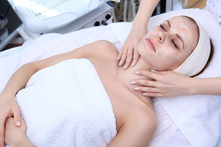 white mask: Beautician makes cleansing, exfoliation, massage in a beauty salon.