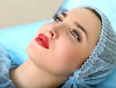 Spa saludable: mujer joven hermosa que tiene tatuaje maquillaje permanente en los labios. De cerca