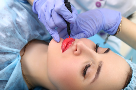 mujer maquillandose: Spa saludable: mujer joven hermosa que tiene tatuaje maquillaje permanente en los labios. De cerca