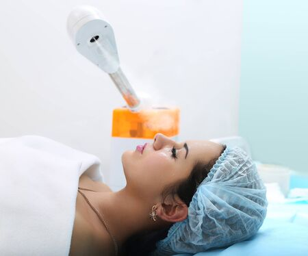 facial steamer: Relaxing during a facial steam treatment at a beauty spa.