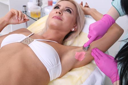 beautiful armpit: Beautician makes waxing armpit hair, beautiful blonde woman in a beauty salon.