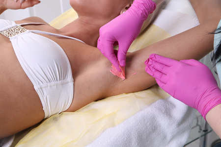 armpit hair: Beautician makes waxing armpit hair, beautiful blonde woman in a beauty salon.
