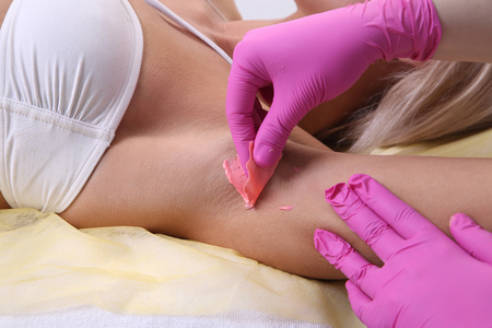 armpit hair: Beautician makes waxing armpit hair, beautiful blonde woman in a beauty salon.