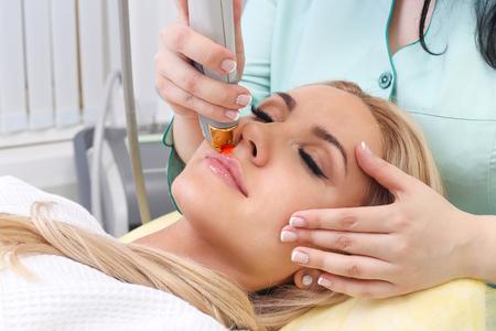 depilacion: La depilación láser en el salón de belleza. Mujer que tiene la eliminación del vello facial. Equipo láser de depilación en el fondo.