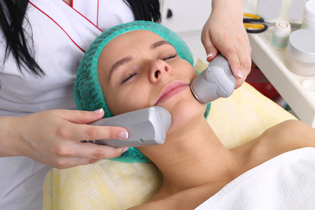 Close up of young woman in hat receiving electric ultrasonic facial massage at beauty salon. Procedure vibro-cell electrotherapy.