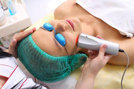 elasticidad: mujer joven y hermosa toma el tratamiento del procedimiento con l�ser fr�o en el sal�n de belleza. Foto de archivo