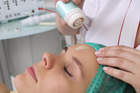 stimulator: People, beauty, spa, cosmetology and technology concept - close up of beautiful young woman lying with closed eyes having face massage by massager in spa.