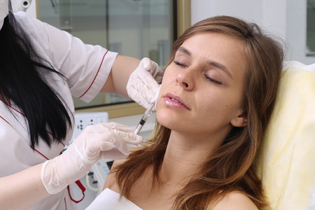 gets: Mesotherapy. Beautiful woman gets an injection in her face. Stock Photo