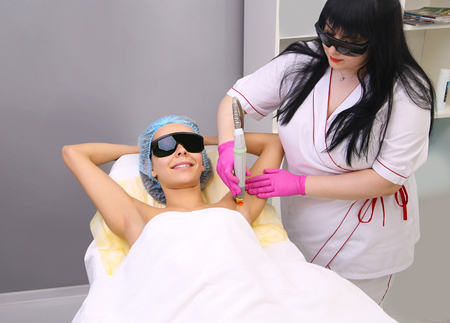 underarm: Blonde woman having underarm Laser hair removal epilation. Laser treatment in cosmetic salon. Stock Photo