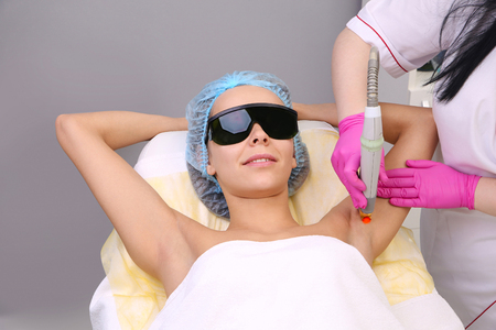 Blonde woman having underarm Laser hair removal epilation. Laser treatment in cosmetic salon. Standard-Bild
