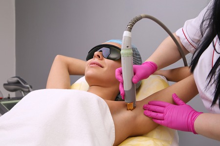 Blonde woman having underarm Laser hair removal epilation. Laser treatment in cosmetic salon. Stock Photo