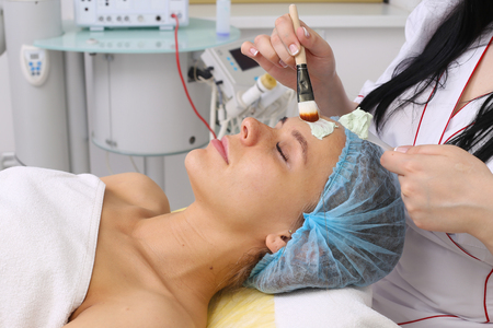 cosmetician: Cosmetician applying facial mask to the face of young beautiful woman in spa salon