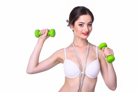 Young woman posing with dumbbells isolated on white background.