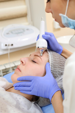 rf: Close up of young woman receiving electric ultrasonic facial massage at beauty salon.