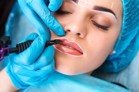 Cosmetologist making permanent makeup on womans face Archivio Fotografico