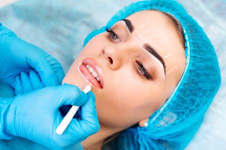 Cosmetologist faire le maquillage permanent sur le visage d'une femme