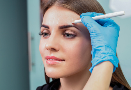 marking up: Permanent eyebrow make up. Stock Photo