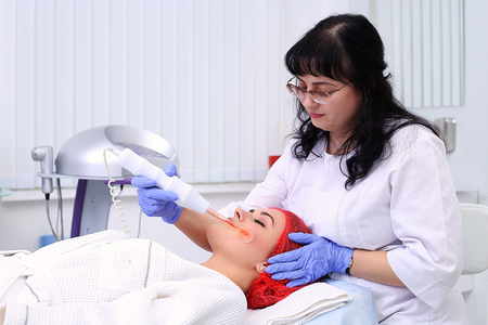Receiving electric darsonval facial massage procedure. Stock Photo