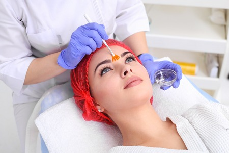 cosmetician: Beautiful young woman is getting face skin treatment. Stock Photo
