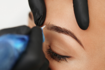 Cosmetologist applying permanent make up on eyebrows- eyebrow tattoo Archivio Fotografico