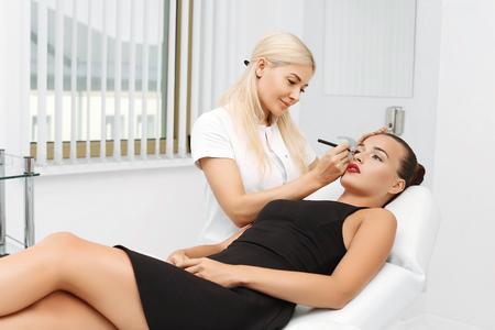 Cosmetóloga aplica maquillaje permanente en los ojos, primer plano