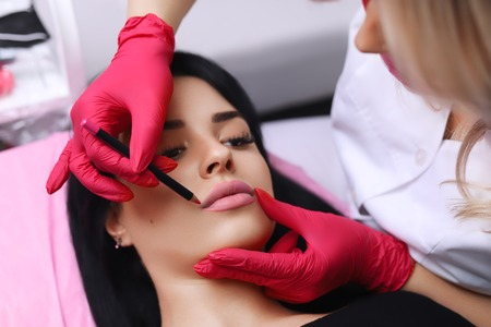Cosmetologist making permanent makeup on womans face Imagens