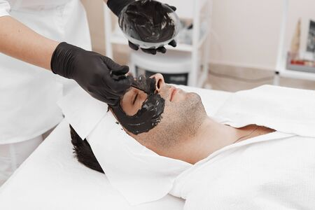 Spa therapy for men receiving facial black mask.