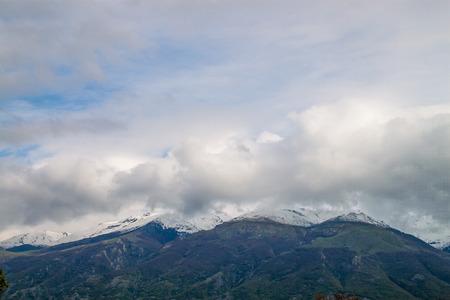 Snowed peaks covered in clouds photo