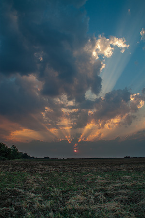 cultivated land: Inspiring sunset over cultivated land with dramatic sky, clouds and sunbeams