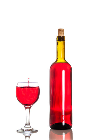 Wine bottle with a falling drop of wine in a glass photo
