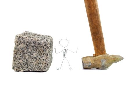 Eine Büroklammer Figur stehend zwischen Pflasterstein und einem Hammer