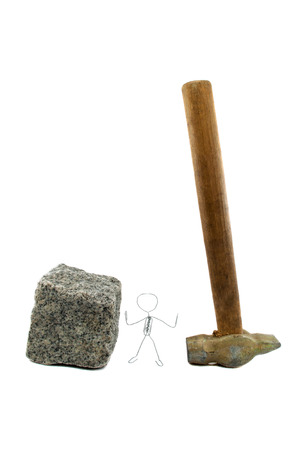 A paperclip figure standing between paving stone and a hammer photo