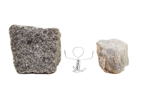 A paperclip figure sitting between paving stone and a marble stone photo