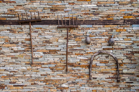 agricultural tools: Old agricultural tools hanging on a dry stone wall