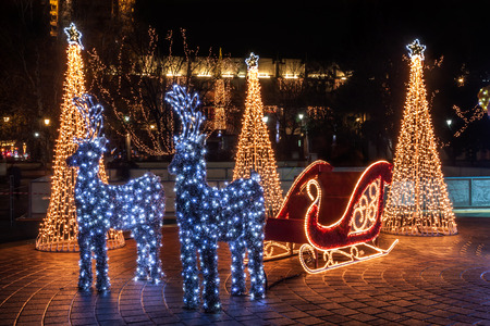 Santa Claus sleigh and two reindeer decorated with lights photo