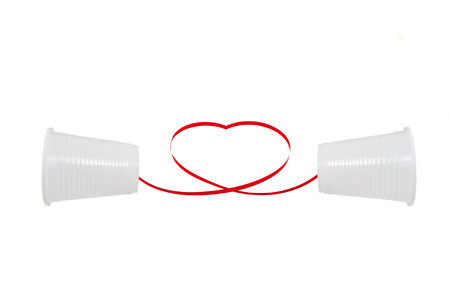Long distance relationship concept. 2 white plastic cups connected with a red thread photo