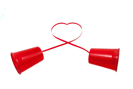Long distance relationship concept. 2 red plastic cups connected with a red thread photo