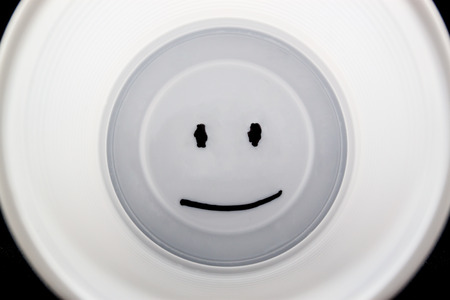 White plastic cup with a smiley face on the bottom photo