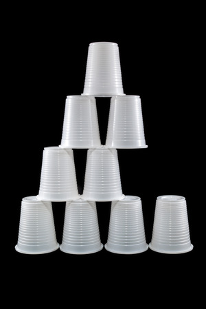 missing link: Pyramid made of plastic cups isolated on black. Missing link concept.