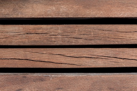 Closeup of an old bench planks. The paint so weathered it has started to peel. photo