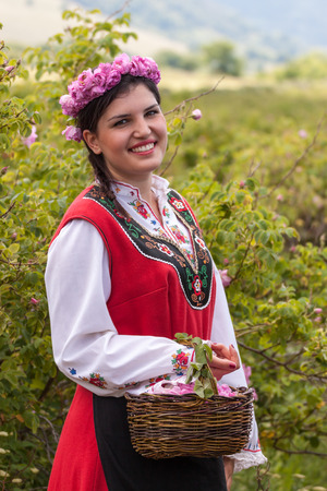 bulgaria girl: Woman dressed in a Bulgarian traditional folklore costume picking roses in a garden, as part of the summer regional ritual in Rose valley, Bulgaria. Stock Photo